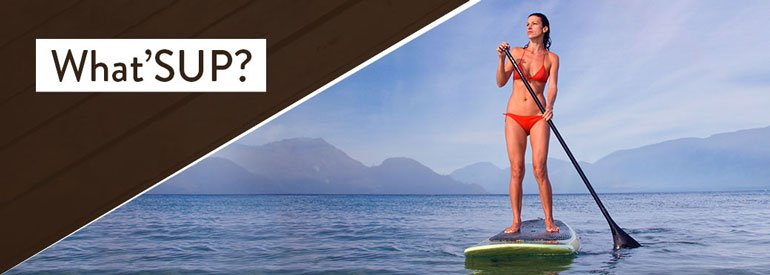 Main image for What'SUP McKinley Beach ( Kelowna BC waterfront community and beachfront community ) post, showing a woman on a stand up paddleboard paddleboarding on the lake